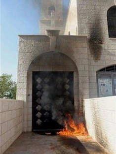 Flames are seen at the entrance of an Anglican church hit by a firebomb in Nablus. Photo: AP